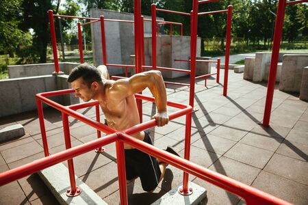 Young muscular shirtless caucasian man doing pull-ups on horizontal bar at playground in sunny summers day. Training his upper body outdoors. Concept of sport, workout, healthy lifestyle, wellbeing. Standard-Bild - 128911015