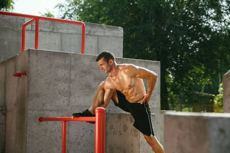 Young muscular shirtless caucasian man doing stretching exercises at playground in sunny summers day. Training his upper body outdoors. Concept of sport, workout, healthy lifestyle, wellbeing. Standard-Bild - 128911021