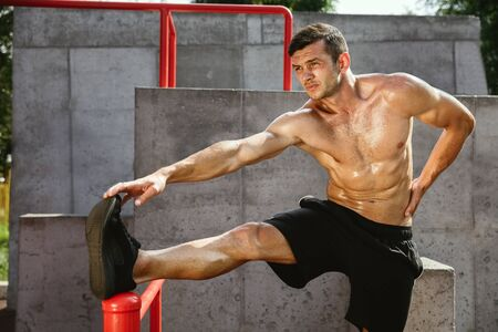 Young muscular shirtless caucasian man doing stretching exercises at playground in sunny summers day. Training his upper body outdoors. Concept of sport, workout, healthy lifestyle, wellbeing. Standard-Bild - 128911026
