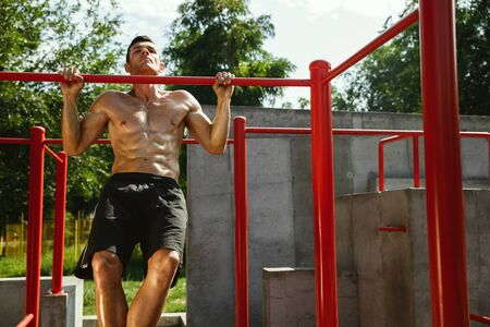 Young muscular shirtless caucasian man doing pull-ups on horizontal bar at playground in sunny summers day. Training his upper body outdoors. Concept of sport, workout, healthy lifestyle, wellbeing.