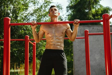 Young muscular shirtless caucasian man doing pull-ups on horizontal bar at playground in sunny summers day. Training his upper body outdoors. Concept of sport, workout, healthy lifestyle, wellbeing. Standard-Bild - 128911029