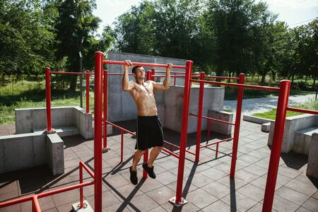 Young muscular shirtless caucasian man doing pull-ups on horizontal bar at playground in sunny summers day. Training his upper body outdoors. Concept of sport, workout, healthy lifestyle, wellbeing. Standard-Bild - 128911033