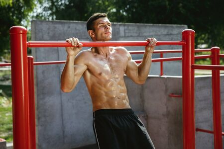 Young muscular shirtless caucasian man doing pull-ups on horizontal bar at playground in sunny summers day. Training his upper body outdoors. Concept of sport, workout, healthy lifestyle, wellbeing. Standard-Bild - 128911032