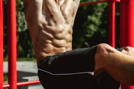 Young muscular shirtless caucasian man doing crunches on horizontal bar at playground in sunny summers day. Training upper body outdoors. Concept of sport, workout, healthy lifestyle, wellbeing. Stockfoto