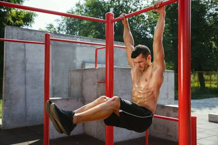 Young muscular shirtless caucasian man doing crunches on horizontal bar at playground in sunny summers day. Training upper body outdoors. Concept of sport, workout, healthy lifestyle, wellbeing. Banco de Imagens