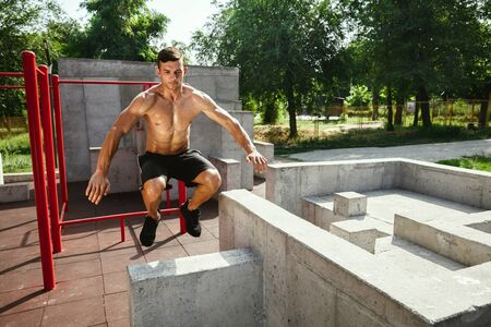 Young muscular shirtless caucasian man jumping above horizontal bar at playground in sunny summers day. Training his upper body outdoors. Concept of sport, workout, healthy lifestyle, wellbeing.