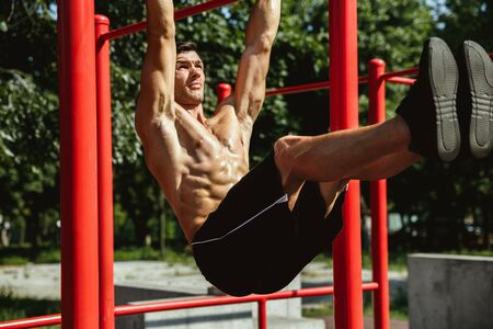 Young muscular shirtless caucasian man doing pull-ups on horizontal bar at playground in sunny summers day. Training his upper body outdoors. Concept of sport, workout, healthy lifestyle, wellbeing. Standard-Bild - 128911042