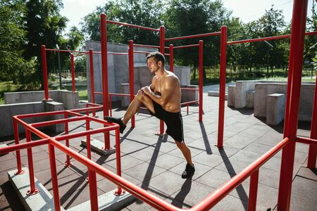 Young muscular shirtless caucasian man doing stretching exercises at playground in sunny summers day. Training his upper body outdoors. Concept of sport, workout, healthy lifestyle, wellbeing. Standard-Bild - 128911046