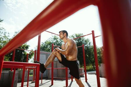 Young muscular shirtless caucasian man doing stretching exercises at playground in sunny summers day. Training his upper body outdoors. Concept of sport, workout, healthy lifestyle, wellbeing. Standard-Bild - 128911059