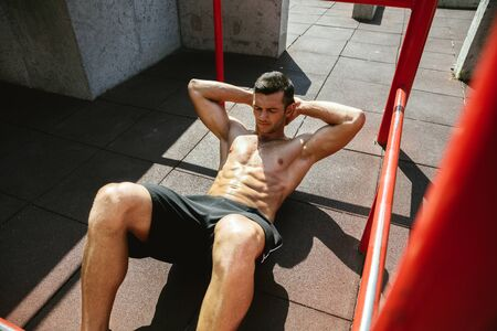 Young muscular shirtless caucasian man doing crunches on horizontal bar at playground in sunny summers day. Training upper body outdoors. Concept of sport, workout, healthy lifestyle, wellbeing. Standard-Bild - 128911065
