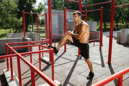 Young muscular shirtless caucasian man doing stretching exercises at playground in sunny summers day. Training his upper body outdoors. Concept of sport, workout, healthy lifestyle, wellbeing. Standard-Bild - 128911067