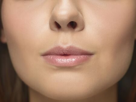 Close-up portrait of young womans face. Female model with well-kept skin and big lips. Concept of womens health and beauty, cosmetology, cosmetics, self-care, body and skin care. Anti-aging. Banco de Imagens
