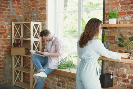 New life. Young couple moved to a new house or apartment. Look happy and confident. Family, moving, relations, first home concept. Unpacking boxes with their plants, books, put things on shelves.