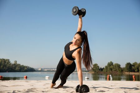 Young healthy woman training upper body with weights at the beach. Single caucasian female model practicing at the river side in sunny day. Concept of healthy lifestyle, sport, fitness, bodybuilding. Stok Fotoğraf - 129048303