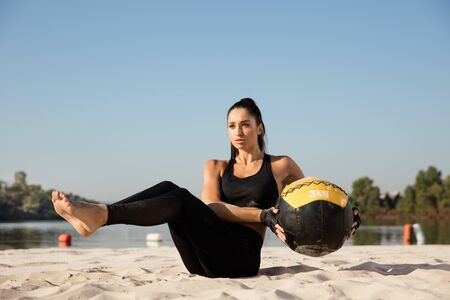Young healthy woman training upper body with ball at the beach. Single caucasian female model training air at the river side in sunny day. Concept of healthy lifestyle, sport, fitness, bodybuilding.