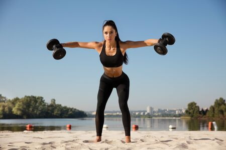 Young healthy woman training upper body with weights at the beach. Single caucasian female model practicing at the river side in sunny day. Concept of healthy lifestyle, sport, fitness, bodybuilding. Stok Fotoğraf - 129048033