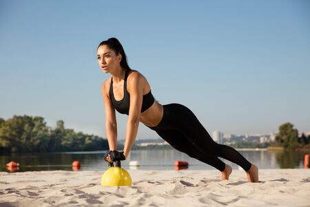 Young healthy woman training upper body with weights at the beach. Single caucasian female model training air at the river side in sunny day. Concept of healthy lifestyle, sport, fitness, bodybuilding. Stok Fotoğraf