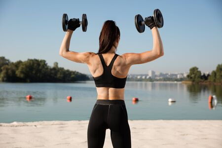 Young healthy woman training upper body with weights at the beach. Single caucasian female model practicing at the river side in sunny day. Concept of healthy lifestyle, sport, fitness, bodybuilding.