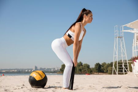 Young healthy woman stretching with the ball at the beach. Single caucasian female model practicing at the river side in sunny day. Concept of healthy lifestyle, sport, fitness, bodybuilding.