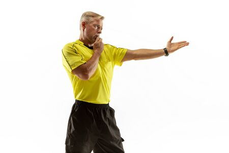 Referee gives directions with gestures to football or soccer players while gaming isolated on white studio background. Concept of sport, rules violation, controversial issues, obstacles overcoming. Stock Photo