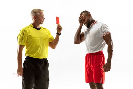 Referee showing a red card to a displeased african-american football or soccer player while gaming isolated on white background. Concept of sport, rules violation, controversial issues, emotions.