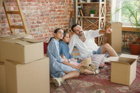 Nouvelle vie. La famille adulte a déménagé dans une nouvelle maison ou un nouvel appartement. Les conjoints et les enfants ont l'air heureux et confiants. Déménagement, relations, nouveau concept de vie. Déballer des cartons avec leurs affaires, jouer ensemble.