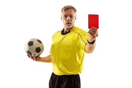 Árbitro sosteniendo la pelota y mostrando una tarjeta roja a un jugador de fútbol o fútbol mientras juega sobre fondo blanco de estudio. Concepto de deporte, violación de reglas, temas controvertidos, superación de obstáculos.