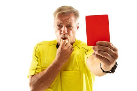 Árbitro que muestra una tarjeta roja y gesticula a un jugador de fútbol o de fútbol mientras juega aislado sobre fondo blanco de estudio. Concepto de deporte, violación de reglas, temas controvertidos, superación de obstáculos. Foto de archivo