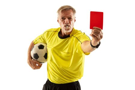 Referee holding ball and showing a red card to a football or soccer player while gaming on white studio background. Concept of sport, rules violation, controversial issues, obstacles overcoming. Stock Photo