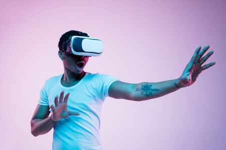 Young african-american mans playing in VR-glasses in neon light on gradient background. Male portrait. Concept of human emotions, facial expression, modern gadgets and technologies. Touches something.