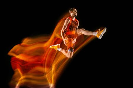 High flight. Young caucasian basketball player of red team in action and motion in mixed light over dark studio background. Concept of sport, movement, energy and dynamic, healthy lifestyle.