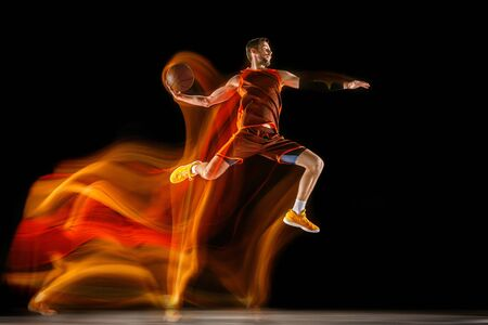 The fire tracks. Young caucasian basketball player of red team in action and jump in mixed light over dark studio background. Concept of sport, movement, energy and dynamic, healthy lifestyle.