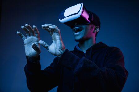 Giovane uomo afroamericano in occhiali VR in luce al neon su sfondo blu. Ritratto maschile. Concetto di emozioni umane, espressione facciale, gadget e tecnologie moderne. Toccare qualcosa durante il gioco.