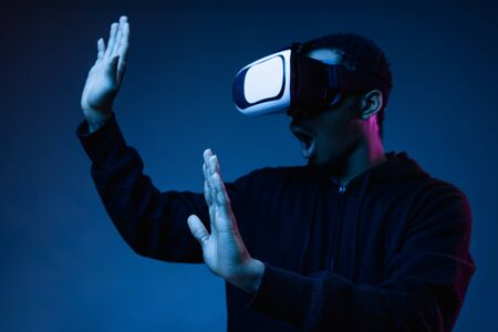 Young african-american mans playing in VR-glasses in neon light on blue background. Male portrait. Concept of human emotions, facial expression, modern gadgets and technologies. Look astonished.