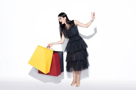 Young brunette woman in black dress shopping on white background. Attractive caucasian female model. Finance, black friday, cyber monday, sales, autumn concept. Copyspace. Shocked, astonished.