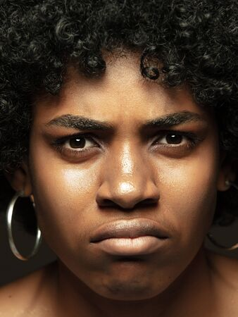 Close up portrait of young, emotional african-american woman. Highly detail photoshot of female model with well-kept skin and bright facial expression. Concept of human emotions. Disgusted, doubts. Banque d'images