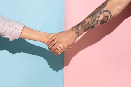 Closeup shot of human holding hands isolated on blue-pink studio background. Concept of human relations, friendship, partnership, family. Copyspace. Stock Photo