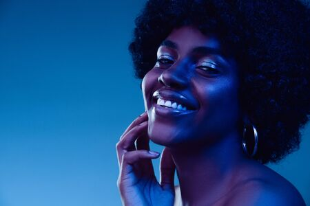 Marvelous night. Portrait of female fashion model in neon light on gradient background. Beautiful african woman with trendy make-up and well-kept skin. Vivid style, beauty, cosmetics concept. Фото со стока