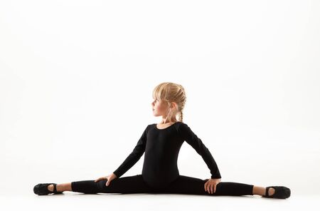 Female flexible little gymnast is practicing isolated on white background. Caucasian blonde girl in black sportsuit training in athletics exercises. Concept of sport, childhood, healthy lifestyle. Stockfoto