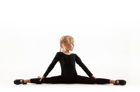 Female flexible little gymnast is practicing isolated on white background. Caucasian blonde girl in black sportsuit training in athletics exercises. Concept of sport, childhood, healthy lifestyle. Stok Fotoğraf
