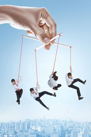 Conceptual image of businessman puppet on gray background. Caucasian male model trying not to falling down being manipulated by his boss. Business, office problems concept.