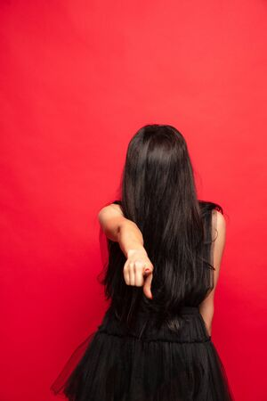 Young brunette woman in black hat and costume on red background. Attractive caucasian female model. Halloween, black friday, cyber monday, sales, autumn concept. Copyspace. Pointing, scary choosing.
