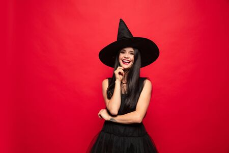 Young brunette woman in black hat and costume on red background. Attractive caucasian female model. Halloween, black friday, cyber monday, sales, autumn concept. Happy smiling.