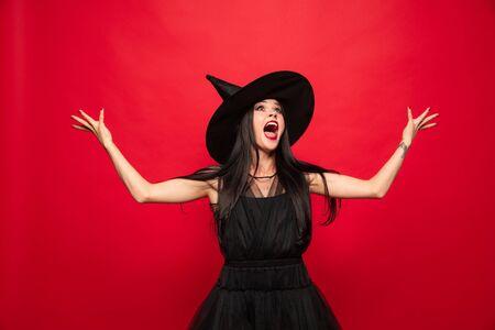 Mujer joven morena con sombrero negro y traje sobre fondo rojo. Modelo femenino caucásico atractivo. Halloween, viernes negro, cyber monday, ventas, concepto de otoño. Gritos de miedo, riendo. Foto de archivo