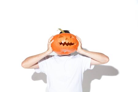 Young man in white shirt on white background. Attractive caucasian male model. Halloween, black friday, cyber monday, sales, autumn concept. Holding pumpkin as his own head. Stock Photo