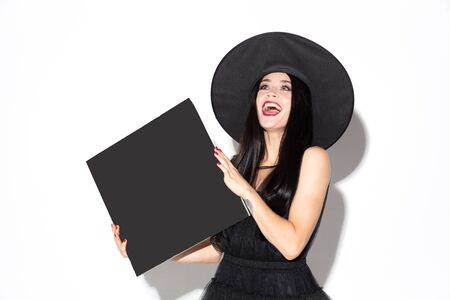 Young brunette woman in black hat and costume on white background. Attractive caucasian female model. Halloween, black friday, cyber monday, sales, autumn concept. Holding empty sheet for your ad.