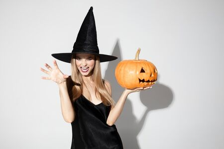 Young blonde woman in black hat and costume on white background. Attractive caucasian female model posing. Halloween, black friday, cyber monday, sales, autumn concept. Copyspace. Holding a pumpkin.