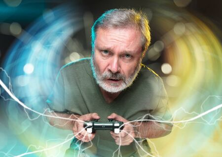 Breathtaking new life. Senior man holding a video game controller isolated on colorful background. Full of emotions. Leisure activity. Has the worst videogames team. Trying to get the highest level. Stok Fotoğraf