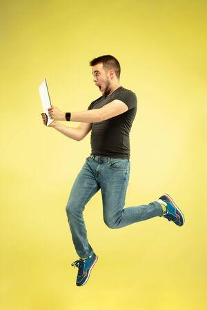 Ganzaufnahme des glücklichen springenden Mannes mit den Geräten lokalisiert auf gelbem Hintergrund. Moderne Technologien, Konzept der Wahlfreiheit, Konzept der Emotionen. Mit Laptop und Smartwatches im Flug.