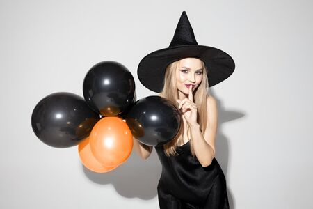 Young blonde woman in black hat and costume on white background. Attractive caucasian female model posing. Halloween, black friday, cyber monday, sales, autumn concept. Copyspace. Holding balloons. Stock Photo